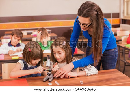 Children working with microscope on creative workshop on biology class. Young teacher is casualy clothed - stock photo