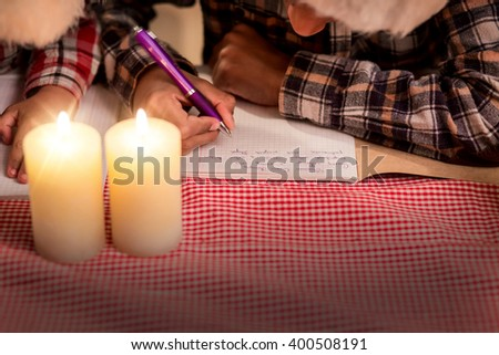Children write letter on Christmas. Young boys writing Christmas letter. Dear Santa, come to us. Expressing holiday thoughts. - stock photo