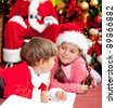 Children writing a Christmas letter for Santa Claus - stock photo