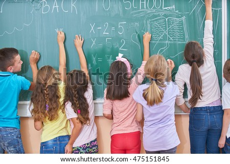 Children writing on blackboard at modern school.