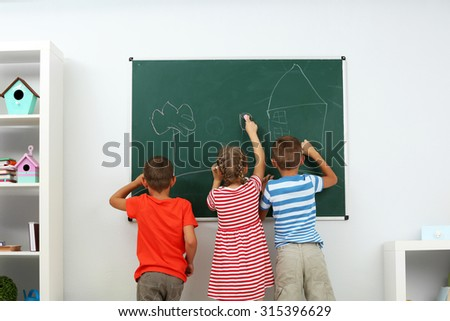Children writing on blackboard at school - stock photo