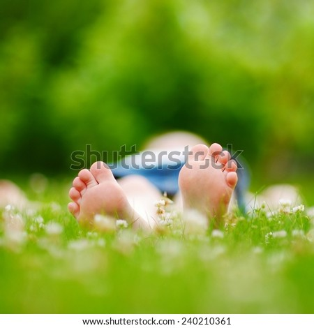 Childrens feet on grass outdoors in summer park