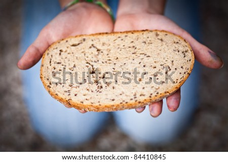 childrens hand giving a slice of bread - stock photo