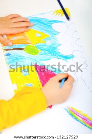 Childrens hand with pencil draws the house - stock photo