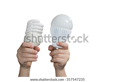 Childrens hands are raised up holding energy-saving and led lamps isolated on a white background