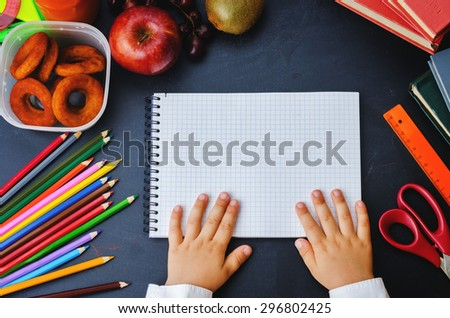childrens hands holding notebook on a blackboard. school concept. the toning. selective focus - stock photo