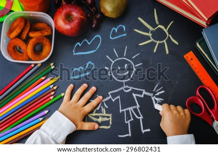 childrens hands writing on a blackboard. school concept. the toning. selective focus - stock photo