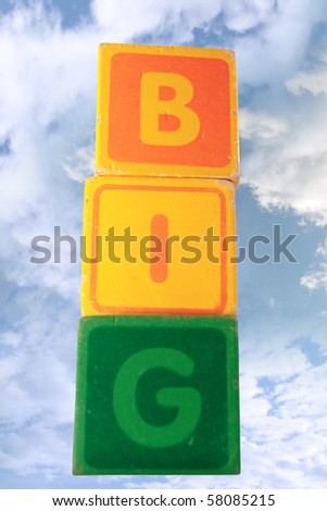 childrens toy letter building blocks against a cloudy background spelling big - stock photo