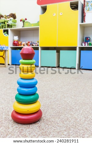 childrens toy pyramid on the floor in a kindergarten - stock photo