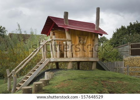 Childrens wooden playhouse with slide - stock photo