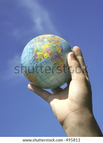 childs hand and globe