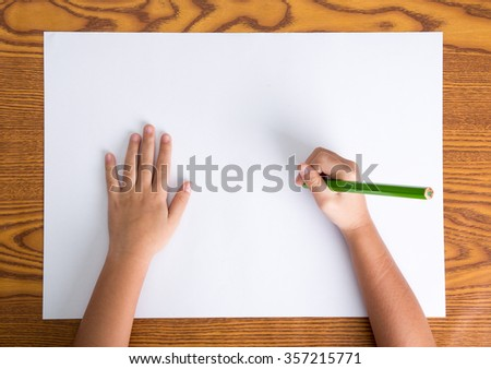 childs hands drawing on a blank paper - stock photo