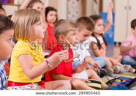 Childs playing musical instruments in classroom. - stock photo