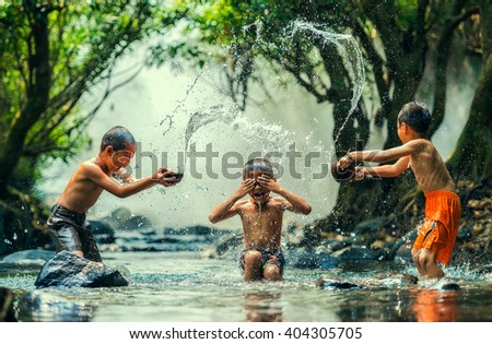 Childs splashing in the river - stock photo
