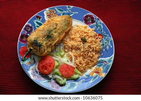 chile relleno is a Mexican dish which is a Poblano pepper stuffed with cheese or meat fried with a batter of egg. The dish may be served with some Mexican rice and some salad - stock photo