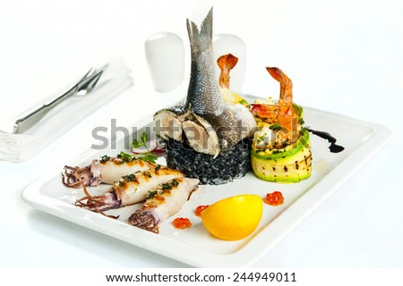 Chile Sea Bass (black sea bass) served with Black Risotto, Herbs ,Vegetables and Squid - stock photo