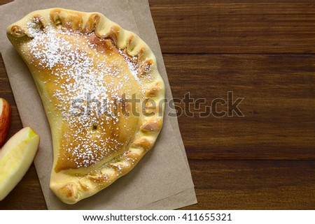 Chilean apple empanada with icing sugar, photographed overhead on dark wood with natural light