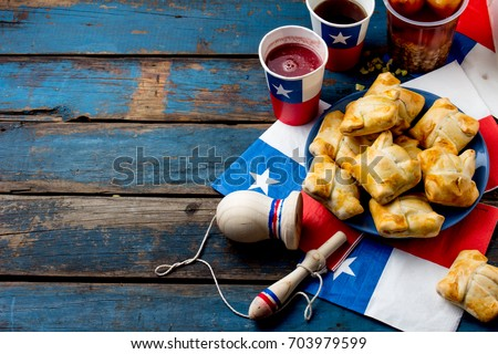 Chilean independence day concept. fiestas patrias. Chilean typical dish and drink on independence day party. Mini empanadas, mote con huesillo, wine with toasted flour chicha and tipical play emboque.