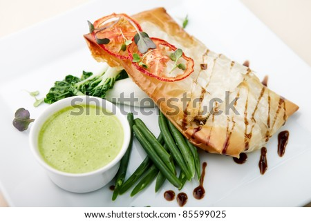 Chilean sea bass in papilliote with sauce - stock photo