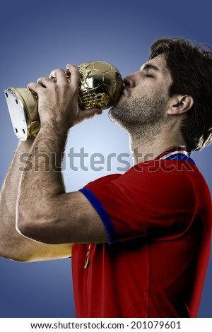 Chilean soccer player, celebrating the championship with a trophy in his hand. On a blue background.