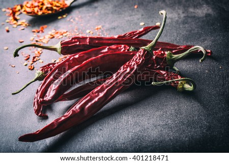 Chili. Chili peppers. Several dried chilli peppers and crushed peppers on an old spoon spilled around. Mexican ingredients - cuisine. - stock photo