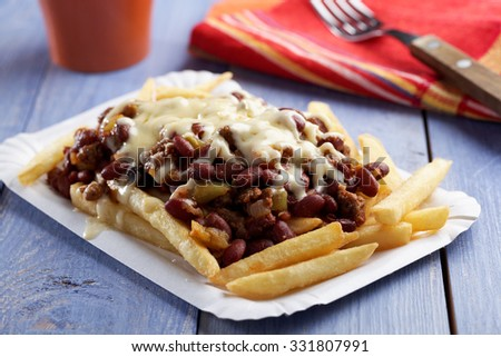 Chili con carne and French fries on a paper plate - stock photo