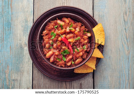 Chili Con Carne in bowl with tortilla chips on wooden background - stock photo