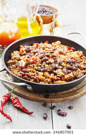 Chili con carne in the frying pan on a wooden table - stock photo