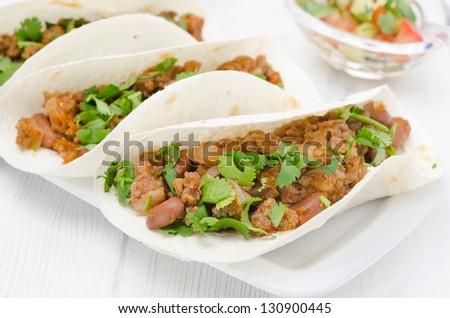 chili con carne in wheat tortillas on a white table closeup - stock photo