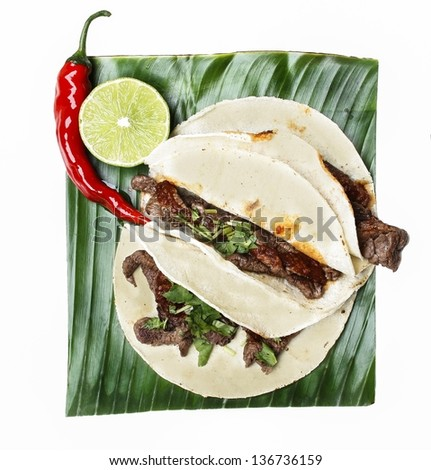 Chili con carne in wheat tortillas on banana leaf, isolated on white - stock photo