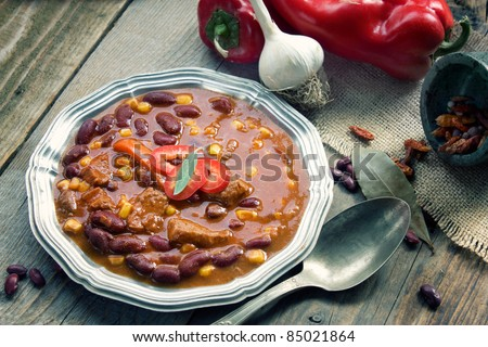 Chili con carne plate. Mexican traditional dish in rustic setting - stock photo