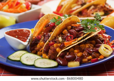 Chili con carne served with corn tacos and hot peppers - stock photo