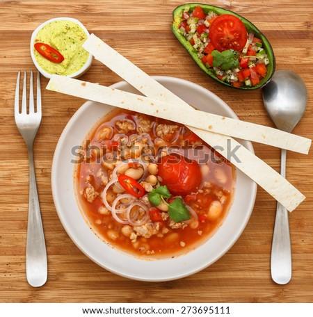 chili con carne soup garnish with tortilla, guakomolle and salad - stock photo