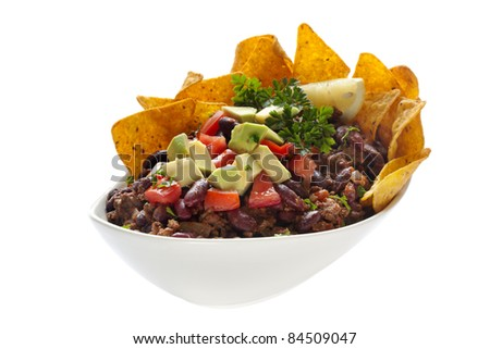 Chili Con Carne, topped with corn chips, avocado and tomato.  Isolated on white. - stock photo