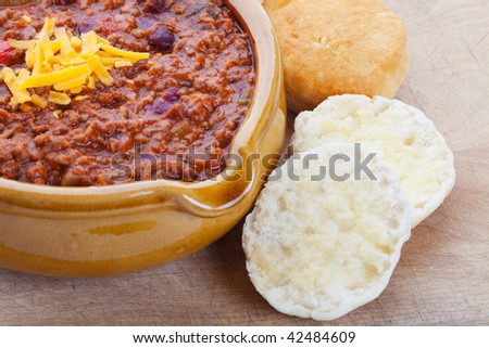 Chili Con Carne topped with shredded cheddar cheese, and served with hot buttered biscuits. - stock photo