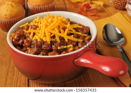 Chili con carne with cheddar cheese and cornbread muffins - stock photo