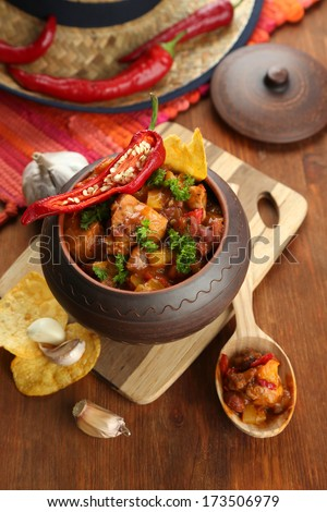 Chili Corn Carne - traditional mexican food, in pot, on napkin, on wooden background - stock photo