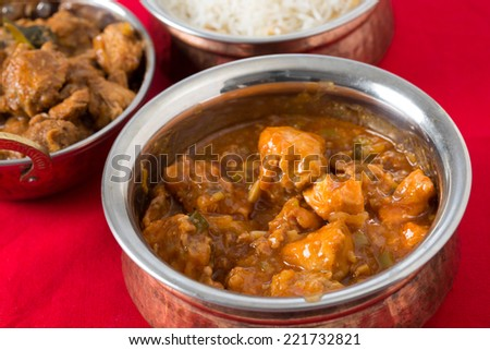 Chili garlic chicken in a serving bowl with rice and chicken malabar behind. - stock photo