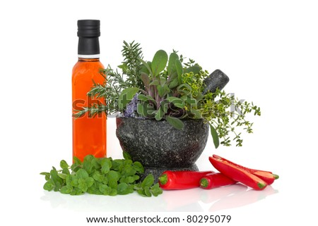Chili oil in a bottle with fresh red pepper chillies and herb leaf sprigs of rosemary, sage, thyme in a granite mortar with pestle with loose oregano leaves, isolated over white background. - stock photo