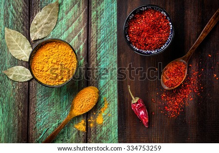 Chili, paprika, turmeric and bay leaves on wooden green and brown background