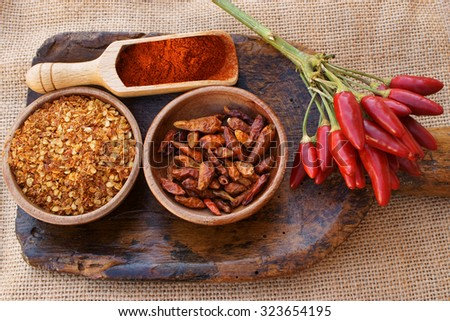 Chili pepper, fresh pods on a bunch, dried in wooden bowl, crushed in a wooden bowl and as powder on wooden scoop is all on an old antique wooden scoop on jute fabric