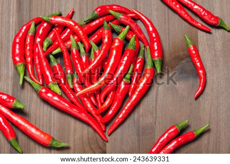 Chili pepper heart on a wooden background - stock photo