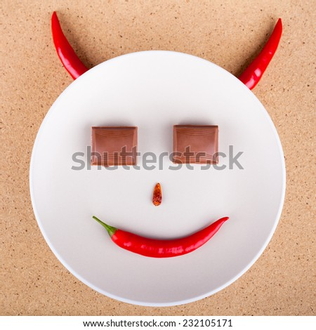 Chili pepper smiling face with chocolate eyes on plate, over wooden background. - stock photo