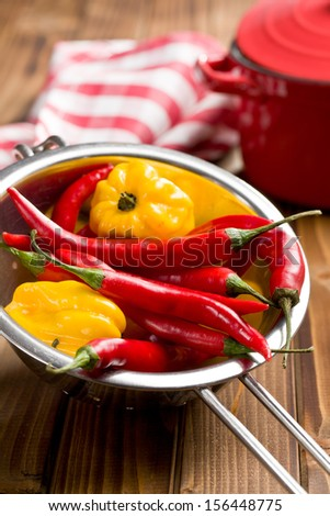 chili peppers and habanero in colander on wooden table - stock photo
