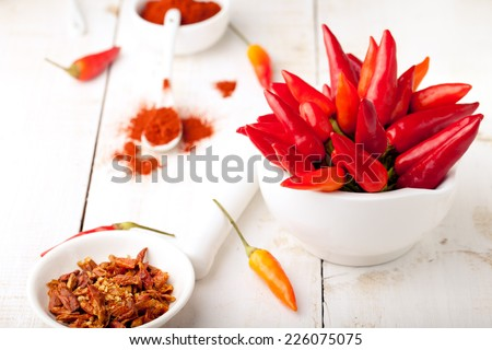 Chili peppers fresh and dry, smoked paprika on a white wooden background - stock photo