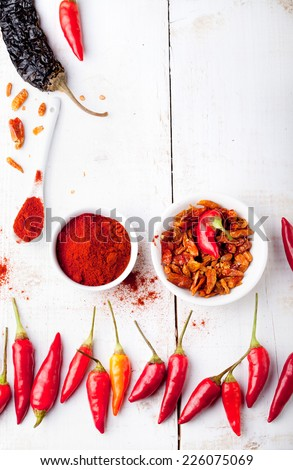 Chili peppers fresh and dry, smoked paprika on a white wooden background. Copy space - stock photo