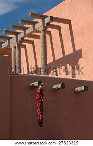 Chili peppers hanging on typical southwestern architectural building. New Mexico. - stock photo