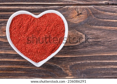 Chili powder in a bowl in the form of heart on a wooden background - stock photo