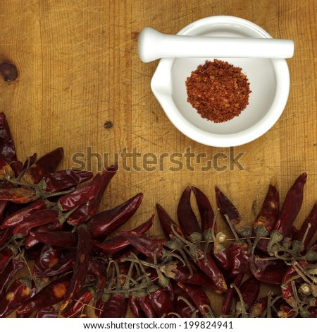 Chili powder in mortar with chillies, close-up - stock photo