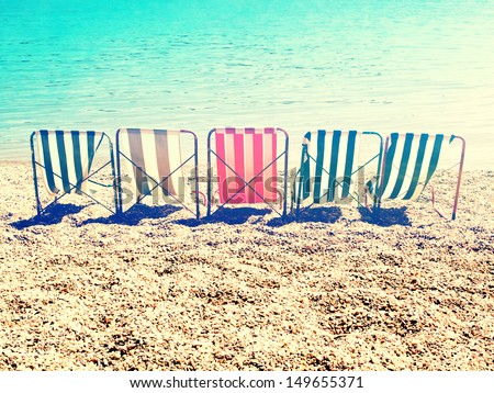 chill on beach with retro stripes sun bed / cross processing style - stock photo